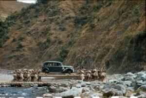 Porters transport a car on long poles across a stream in Nepal, 1948